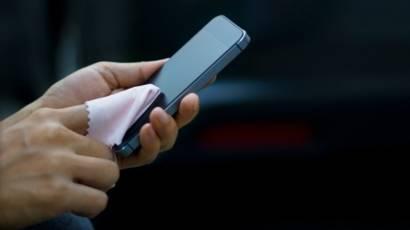 limpando a tela do celular com um pano